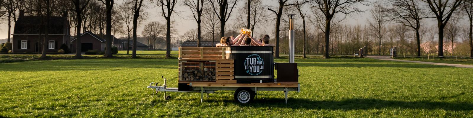 Deze afbeelding laat de mobiele hottub van Tubtoyou zien in een weiland, waarbij jonge mensen proostend genieten van een comfortabel mobiel bad